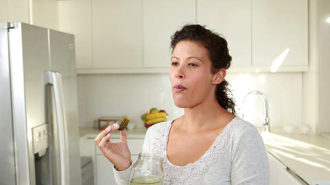 Pregnant woman eating pickles in kitchen Footage