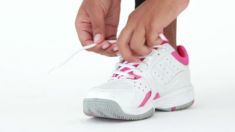 Athletic runner tying up her shoe laces Live Action