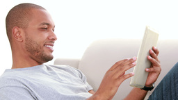Relaxed man scrolling on the tablet Footage