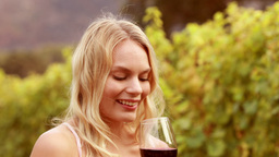 Smiling woman smelling a red wine glass Footage