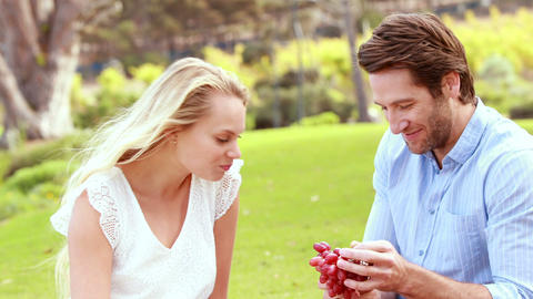 Handsome man giving a red grape to his girlfriend Footage