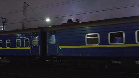 Passenger train arriving to station in the evening Footage