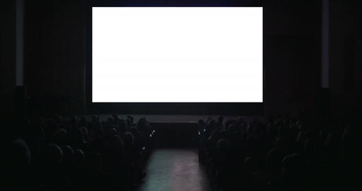 Viewers in dark cinema hall with blank screen Footage