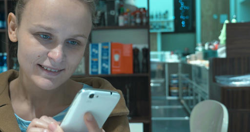 Typing sms on cell and having coffee in cafe Footage