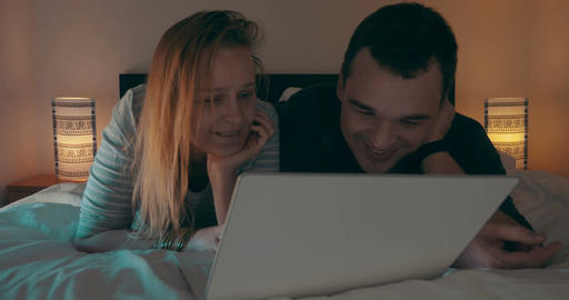 Couple in bed watching movie on laptop Footage