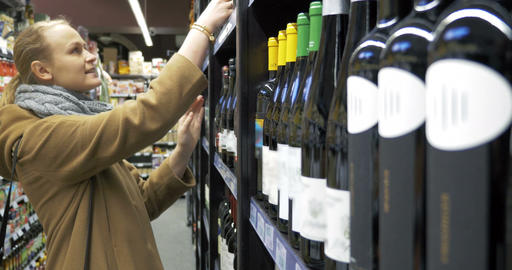 Woman in the store choosing bottle of wine Footage