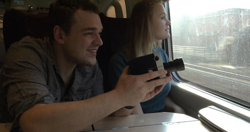 Young couple with retro video camera in train Footage
