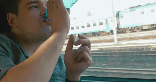 Man taking a headache pill in the train Footage