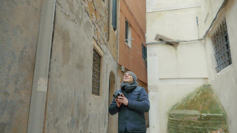 Man filming old architecture with retro camera Live Action