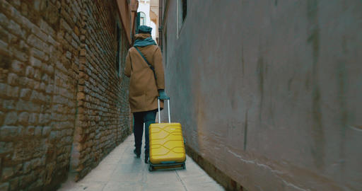 Woman with trolley back walking along the alleyway Footage