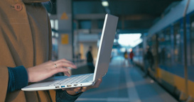 Girl working with laptop at the railway station Footage