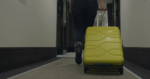 Woman with trolley bag looking for room in hotel Footage