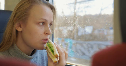 Woman having snack while traveling by train Footage