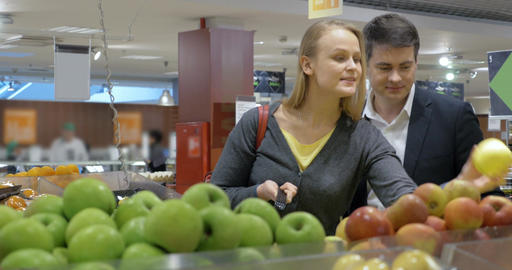Happy young couple buying apples in the supermarket Footage