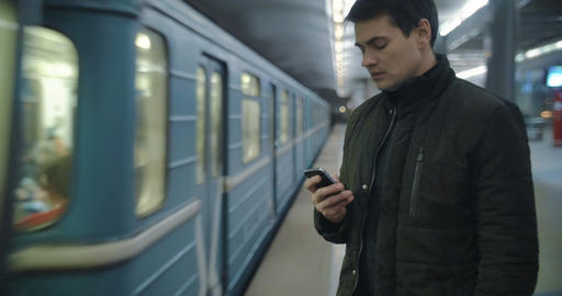 Man typing sms standing on the subway platform Footage