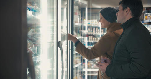 Young couple taking frozen food from fridge in the shop Footage