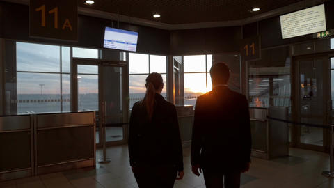 Man and woman enjoying sunset through airport window Footage