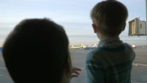 Father and son looking out the window at airport Footage
