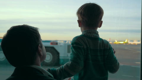 Son and dad looking at airport area through the window Footage