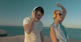 Man and woman getting pleasure from music on beach Footage