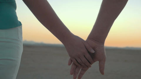 Loving couple holding hands at sunset Footage