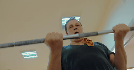 Strong mature man doing arm exercise with crossbar Footage