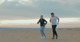 Young couple in headphones running on the beach Footage