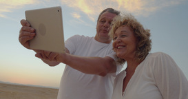 Senior couple using touch pad outdoor on vacation Live Action