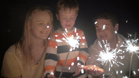 Son and His Parents Catching Sparkles of a Bengale Fire Footage