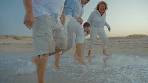 Family walking on the beach and splashing water Footage
