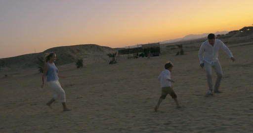 Parents and son playing football on the beach Footage
