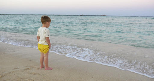Boy Standing in the Incoming Waves Footage