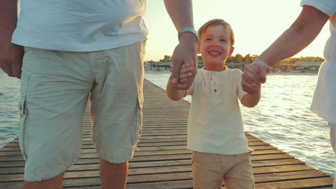 Happy boy walking with grandparents along the pier at sunset Footage