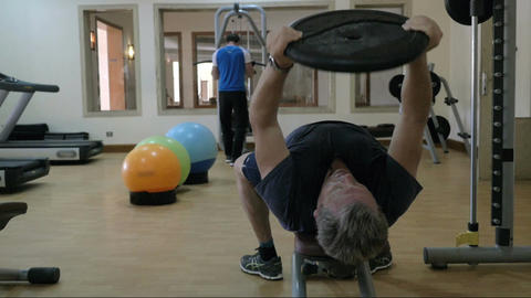 Two men training using sporting equipment in gym Footage