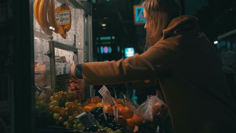 Young woman buys products in the stall outside Footage