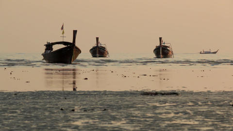 Wooden long-tail boats are floating near a tourist beach at sunset time in Ao Na Live Action