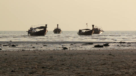 Wooden long-tail boats are floating near a tourist beach at sunset time in Ao Na Footage