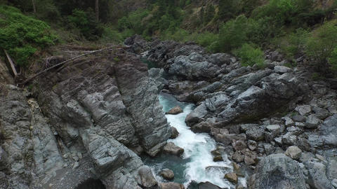 Beautiful River Flowing Through A Rocky Canyon With Green Trees stock footage