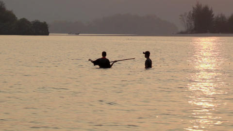 Two Thai men setting nets before low tide in Ao Nang,... Stock Video Footage