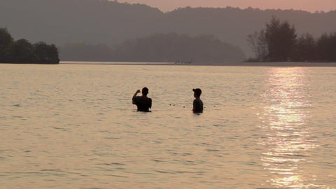Two Thai men setting nets before low tide in Ao Nang, Thailand Footage