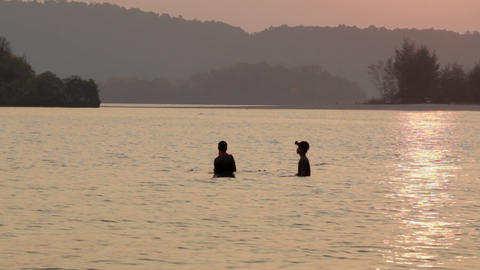 Two Thai men setting nets before low tide in Ao Nang,…, Live Action