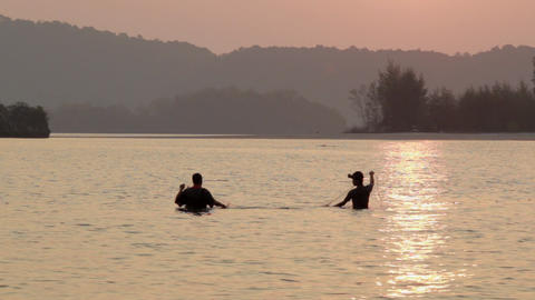 Two Thai men setting nets before low tide in Ao Nang, Thailand Live Action