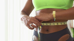 1 Black Woman Measuring Waist With Yellow Tape stock footage