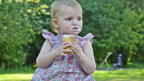 Little girl eats ice cream with appetite, sitting in park on a bench Footage