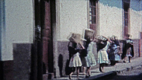 1974: Local townspeople carrying things on their heads Footage