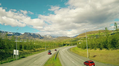 Riding Cars And Floating Clouds On A Background Of Mountains stock footage