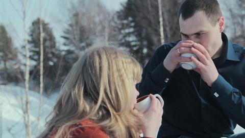 Young couple in love on a winter vacation enjoying the nature and drinking hot t Footage