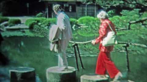 1972: People walking the stepping stones around the zen Japanese style pond Footage