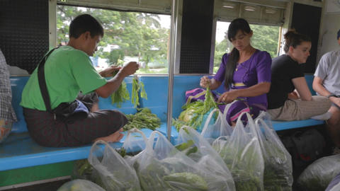 locals peel vegetables inside Myanmar local train Footage