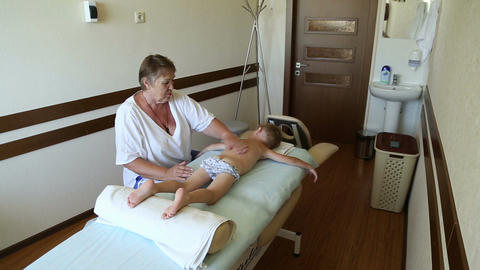 Woman massage therapist doing massage a little boy Live Action